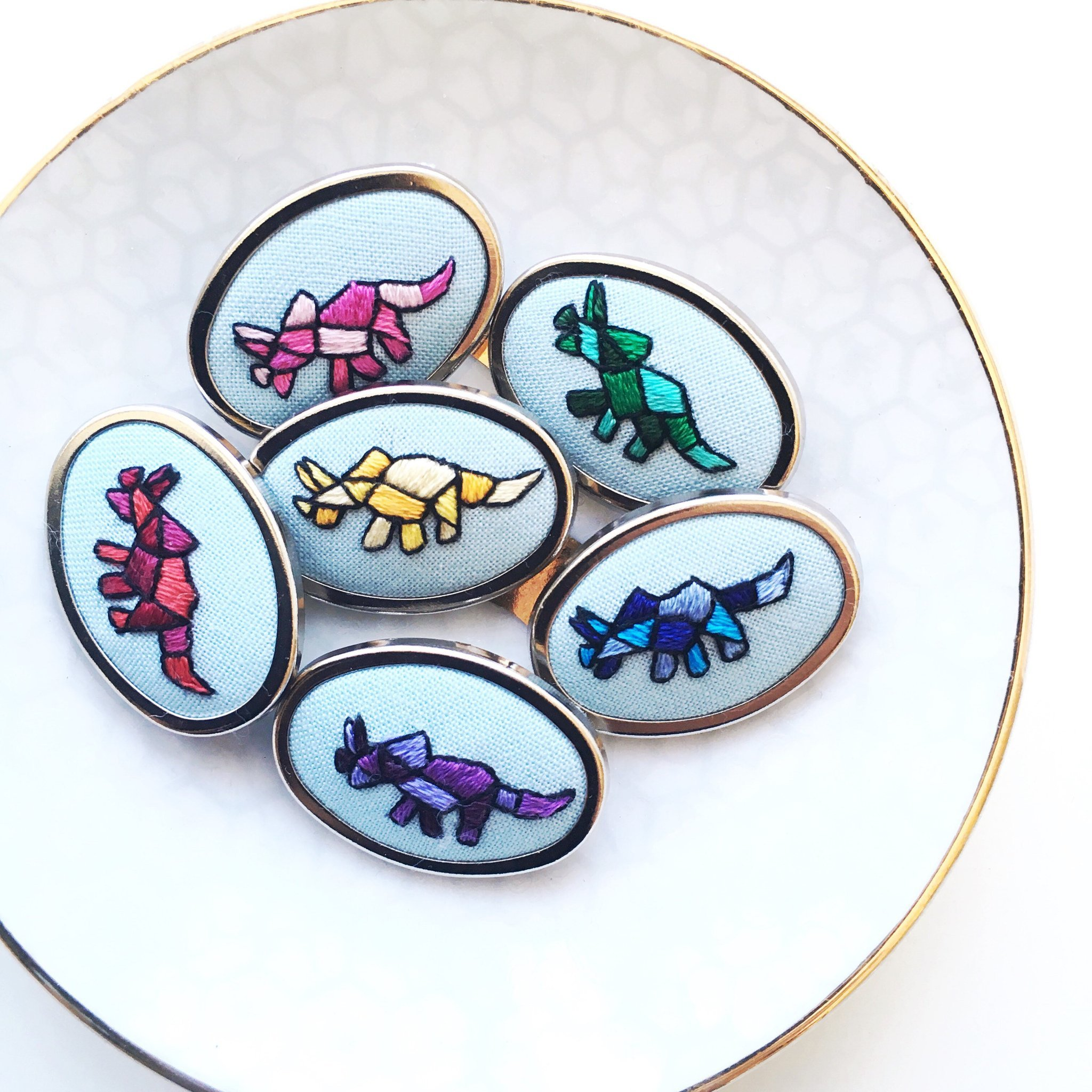 Embroidered Triceratops brooches by Tash Hatcher