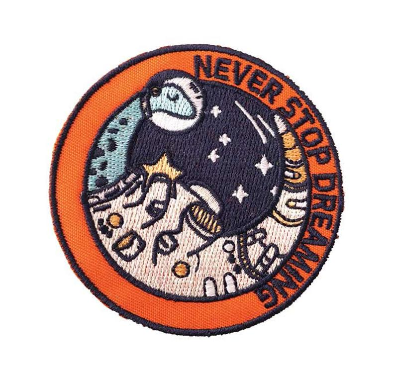 "Embroidered patch design of a sauropod dinosaur in astronaut gear. Reading ""never stop dreaming"""