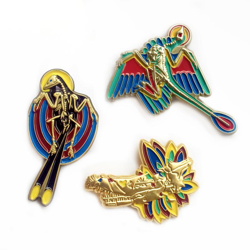 A set of three pins by Greer Stothers featuring feathered dinosaur skeletons in stained glass style
