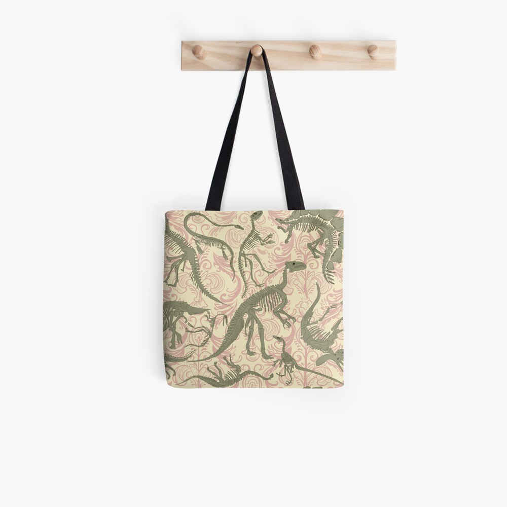 A creme colored tote bag with a pattern of olive green dinosaur skeletons